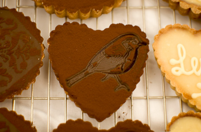Coco&Me - chocolate tart in a shape of a heart with a bird design stamped with cocoa powder